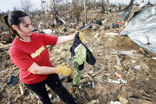 On Thursday, Danna McCord, who lost her mother and stepfather in the Lone Grove tornado, finds a jacket belonging to her sister, who survived. photo By David McDaniel, The Oklahoman