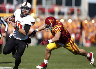 Oklahoma State 's Clint Chelf (10) tries to get by Iowa State's Mitchell Meyers (90) during the college football game between the Oklahoma State University (OSU) and Iowa State University (ISU) at Jack Trice Stadium in Ames, Iowa., Saturday, Oct. 26, 2013. Photo by Sarah Phipps, The Oklahoman