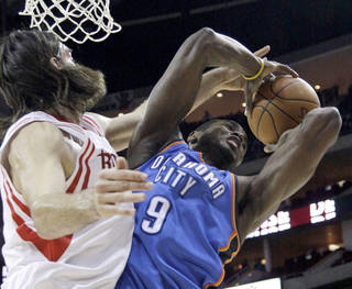 Oklahoma City Thunder's Serge Ibaka (9), of Congo, pulls down a rebound as Houston Rockets' Luis Scola, left, of Argentina, reaches for the ball during the first quarter of an NBA basketball game Wednesday, Jan. 12, 2011, in Houston. (AP Photo/David J. Phillip)