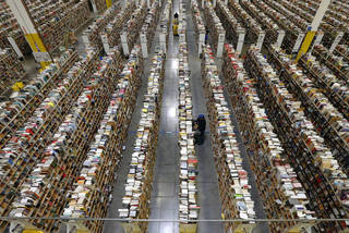 An Amazon.com employee stocks books along one of the many miles of aisles at an Amazon.com Fulfillment Center in Phoenix. AP Photo Ross D. Franklin - AP