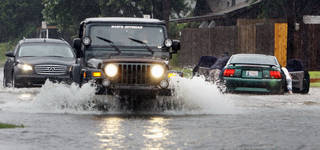 A motorist pushes his vehicle to shallow water on McGee Drive while other drivers brave the flooding as heavy rain falls on July 3, 2010, in Norman. Photo by Steve Sisney, The Oklahoman archives