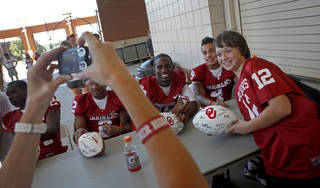 Corey Cargill, 12, of Oklahoma City gets his picture taken OU's Jaz Reynolds, left, and Kenny Stills during the University of Oklahoma's Meet the Sooners Day at Gaylord Family-Oklahoma Memorial Stadium in Norman, Okla., Saturday, August 6, 2011. Photo by Bryan Terry, The Oklahoman