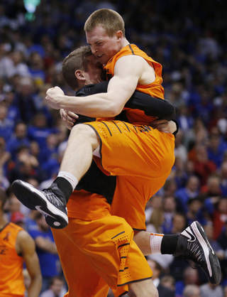 Oklahoma State guard Phil Forte (13) celebrates in the arms of a teammate following an NCAA college basketball game against Kansas in Lawrence, Kan., Saturday, Feb. 2, 2013. Oklahoma State defeated Kansas 85-80. (AP Photo/Orlin Wagner) ORG XMIT: KSOW107