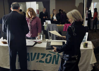 In this photo taken Monday, April 2, 2012, Donna Boulanger, right, of Randolph, Mass. looks over her resume as she waits to speak with Colleen Kingsbury of Travizon during a job fair in Boston. The number of Americans seeking unemployment benefits fell to a four-year low last week, suggesting employers kept hiring in March at a healthy pace. (AP Photo/Elise Amendola) ORG XMIT: MAEA101