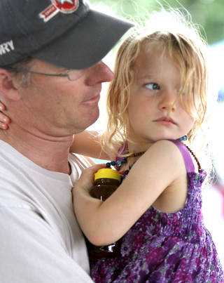 Annaliese Robinson, 3, holds onto her honey and her dad, Ryan, Saturday in Edmond.