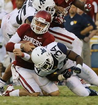 Oklahoma's Trevor Knight (9) is stopped after a run by Ishmael Banks (34) during a college football game between the University of Oklahoma Sooners (OU) and the West Virginia University Mountaineers at Gaylord Family-Oklahoma Memorial Stadium in Norman, Okla., on Saturday, Sept. 7, 2013. Photo by Steve Sisney, The Oklahoman