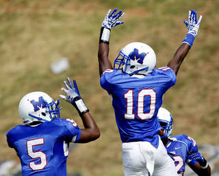 Teammates Alfonzo McMillian, #10, and Quincy Dotson, #5, celebrate in the end zone after McMillian's third quarter touchdown that put the Falcons ahead by a score of 18-0 during the annual Soul Bowl football game between the Douglass Trojans and the Millwood Falcons at Leodies Robinson Field in Oklahoma City on Saturday, Sep. 14, 2013. In background is Andre Clanton, #22. Millwood defeated Douglass, 31-12. Photo by Jim Beckel, The Oklahoman.