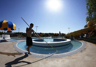 Levi Garrison cleans the Lazy River at the Pelican Bay Aquatic Center on Wednesday.