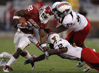 Oklahoma's Roy Finch (22) tries to get past Texas Tech's Brian Duncan (57) and D.J. Johnson (12) during the second half of the college football game between the University of Oklahoma Sooners (OU) and the Texas Tech Red Raiders (TTU) at the Gaylord Family-Oklahoma Memorial Stadium on Saturday, Nov. 13, 2010, in Norman, Okla. Photo by Chris Landsberger, The Oklahoman ORG XMIT: KOD