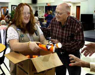 Mikayla Thompson, 13, hands out health record-keeping containers called Vials of Life to John Kelley, 87, and others at Moore's Brand Senior Center as part of a Girl Scout project. Photo by Steve Sisney, The Oklahoman
