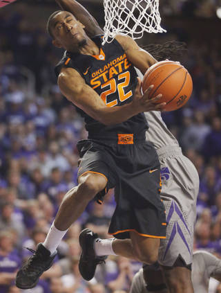 Oklahoma State guard Markel Brown (22) is fouled by Kansas State forward D.J. Johnson during the first half of an NCAA college basketball game in Manhattan, Kan., Saturday, Jan. 4, 2014. (AP Photo/Orlin Wagner)