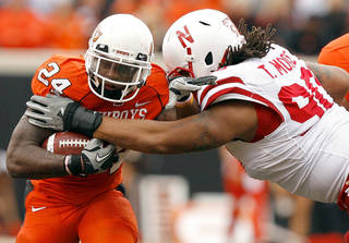 OSU's Kendall Hunter gets past Nebraska's Terrence Moore during the college football game between the Oklahoma State Cowboys (OSU) and the Nebraska Huskers (NU) at Boone Pickens Stadium in Stillwater, Okla., Saturday, Oct. 23, 2010. Photo by Sarah Phipps, The Oklahoman