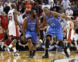 The Thunder's James Harden (13) is congratulated by teammate Kevin Durant (35) after Harden scored against the Miami Heat in the fourth quarter of Wednesday's game. AP photo