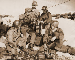 "45TH INFANTRY / 45TH DIVISION / MILITARY / DEFENSE / SOLDIERS / KOREA / EQUIPMENT: ""Thunderbirds Prepare Deadly Greeting to Reds. Five Oklahomans, members of the 45th Division's 189th battalion, are shown cleaning their 155 millimeter howitzer during a lull on the Korean battlefront. Battery C of the 189th was the first unit of the former national guard division to swing into action against the communists in Korea. From left to right are Pfc. Lawrence W. Leighton, 523 SW 34; and Pfc. Joe Brown. Cpl. Bob Boyer, Pfc. Fred L. Marquardt and Pfc. Hale Abernathy, all of Blackwell."" 45th Division News Photo by Ron Pyer. Original photo undated. Published 02/01/1952 in The Oklahoma City Times [LS]."