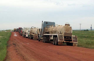 A line of trucks wait to help clean up the site of a saltwater spill Thursday near Mandaree, N.D. AP Photo Josh Wood