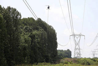This July 8, 2013 photo provided by FirstEnergy shows a helicopter aerial saw trimming trees along a FirstEnergy transmission corridor in Doylestown, Ohio. Electric utility tree-trimmers have made their mark on the picturesque hillside where branches coming into contact with high-power lines helped set off a chain-reaction blackout stretching to Canada and the East Coast and fried household appliances 10 years ago. But the sound of chain saws isn't welcome to tree lovers who now see open skies where tall trees once shaded the power lines and the neighborhood. - AP Photo/HO, FirstEnergy