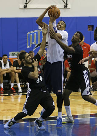 Oklahoma City Thunder's Andre Roberson, center, tries to make a shot between Detroit Pistons' Peyton Siva (34) and Kartavious Caldwell-Pope, right, during an NBA summer league basketball game, Tuesday, July 9, 2013, in Orlando, Fla. (AP Photo/John Raoux) ORG XMIT: DOA113