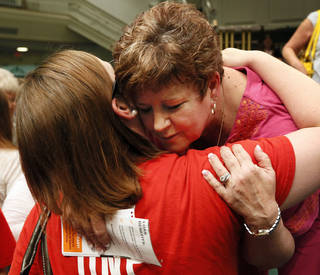 Moore Superintendent Susan Pierce gets a hug from Kingsgate Elementary teacher Jessica Parker after a district staff meeting Wednesday afternoon at Southern Hills Baptist Church. Pierce is retiring and will spend her last weeks at work helping the district begin the rebuilding process after a tornado killed seven students. NATE BILLINGS - THE OKLAHOMAN