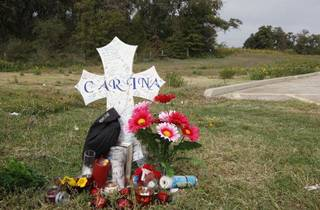 A memorial to Carina Saunders sits behind a grocery store in Bethany near the wooded area where her dismembered body was found stuffed in a duffel bag. (AP Photo/Sue Ogrocki) ORG XMIT: OKSO102 Sue Ogrocki - AP