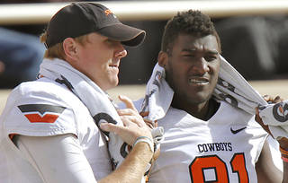 Oklahoma State Cowboys quarterback Brandon Weeden (3) and Justin Blackmon (81) talk on the sideline during the college football game between the Oklahoma State University Cowboys (OSU) and Texas Tech University Red Raiders (TTU) at Jones AT&T Stadium on Saturday, Nov. 12, 2011. in Lubbock, Texas. Photo by Chris Landsberger, The Oklahoman
