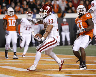 Oklahoma's Trey Millard (33) scores in front of Oklahoma State's Orie Lemon (41) during the Bedlam college football game between the University of Oklahoma Sooners (OU) and the Oklahoma State University Cowboys (OSU) at Boone Pickens Stadium in Stillwater, Okla., Saturday, Nov. 27, 2010. Photo by Bryan Terry, The Oklahoman