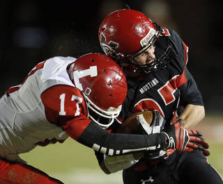 Lawton's Kalin Sadler tackles Mustang's Kale Harper during a game in 2012. Sadler, who is No. 28 on The Oklahoman's Super 30 recruiting list, has received a scholarship offer from New Mexico. Photo by Sarah Phipps, The Oklahoman