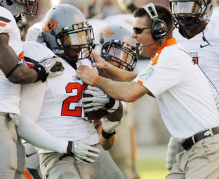 OKLAHOMA STATE UNIVERSITY: OSU head coach Mike Gundy grabs James Thomas (22) late in the fourth quarter after Thomas intercepted a pass to end Texas A&M's final drive during a college football game between the Oklahoma State Cowboys and the Texas A&M Aggies at Kyle Field in College Station, Texas, Saturday, Sept. 24, 2011. OSU won, 30-29. Photo by Nate Billings, The Oklahoman ORG XMIT: KOD