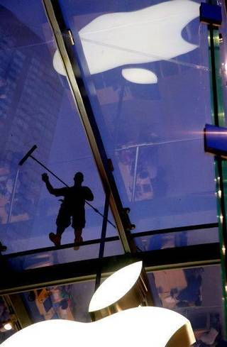 In this July 21, 2011 photo, a window washer works atop the cube-like structure of glass that houses the Apple Store showroom in the Upper West Side of Manhattan. Investors seem to think you want an iPad more than oil, as Apple Inc. became the most valuable company in the United States, surpassing Exxon Mobil Corp. on Wednesday. Apple briefly flirted with the top spot on Tuesday afternoon before settling back slightly below the oil giant. (AP Photo/Craig Ruttle) ORG XMIT: NYCR201