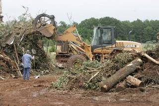 Oklahoma County District 2 workers sort storm debris at Oklahoma County's burn pit near Harrah , Oklahoma May 19 , 2010. Photo by Steve Gooch