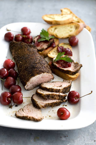 Cherry-topped coffee-roasted pork tenderloin is shown served on a platter. AP Photo MATTHEW MEAD - AP
