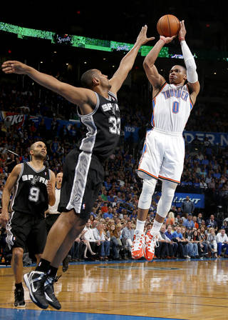 Oklahoma City's Russell Westbrook (0) shoots over San Antonio's Boris Diaw (33) and Tony Parker (9) during an NBA basketball game between the Oklahoma City Thunder and the San Antonio Spurs at Chesapeake Energy Arena in Oklahoma City, Thursday, April 3, 2014. Oklahoma City won 106-94. Photo by Bryan Terry, The Oklahoman