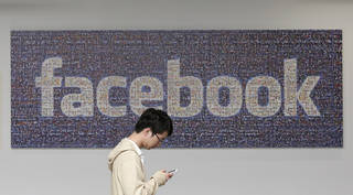 A man walks past a Facebook sign in an office on the Facebook campus in Menlo Park, Calif. AP Photo Jeff Chiu - AP