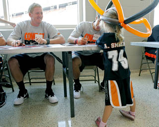 OSU quarterback Brandon Weeden (left) smiles at Megan Trolinger, age 5 of Inola, Oklahoma and her balloon cowgirl hat while Weeden and Clint Chelf (right) sign autographs during Oklahoma State's Fan Appreciation Day at Gallagher-Iba Arena in Stillwater, Oklahoma on Saturday, Aug. 6, 2011. Photo by John Clanton, The Oklahoman ORG XMIT: KOD