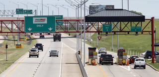 Drivers pass through a toll gate on the Kilpatrick Turnpike Wednesday in Oklahoma City. Photo By Steve Gooch, The Oklahoman
