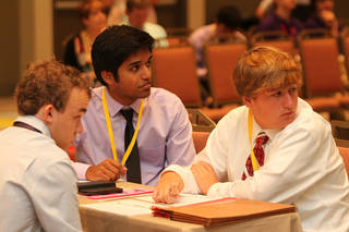 Team Oklahoma competitors, from left, Finn Bender, Steven Kappen and Hunter Antonisse, listen to a question being read by a moderator on June 16 at the National Tournament of Academic Excellence in Orlando. Photo by David Brame, Dynamx Digital Dynamx Digital - Photos by David Brame, Dynamx Digital.