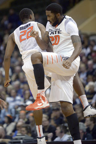 Oklahoma State forward Markel Brown (22) and forward Michael Cobbins (20) celebrate during a timeout in the first half of an NCAA college basketball game against Purdue in Kissimmee, Fla., Thursday, Nov. 28, 2013. (AP Photo/Phelan M. Ebenhack)