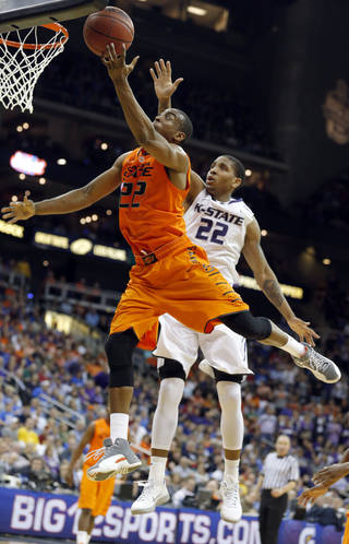 Oklahoma State's Markel Brown (22) shoots a lay up as Kansas State's Rodney McGruder (22) defends during the Phillips 66 Big 12 Men's basketball championship tournament game between Oklahoma State University and Kansas State at the Sprint Center in Kansas City, Friday, March 15, 2013. Photo by Sarah Phipps, The Oklahoman
