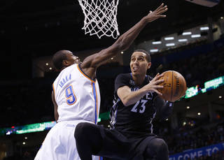 Minnesota Timberwolves guard Kevin Martin (23) moves past Oklahoma City Thunder forward Serge Ibaka (9) for a shot during the first quarter of an NBA basketball game in Oklahoma City, Wednesday, Feb. 5, 2014. (AP Photo/Sue Ogrocki)