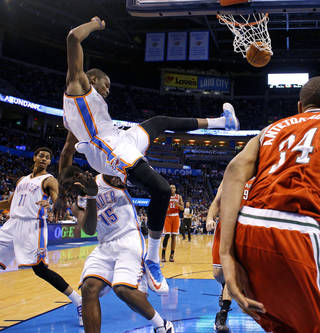 Oklahoma City's Kevin Durant falls onto Reggie Jackson during the Thunder's game vs. Milwaukee on Saturday. Durant told The Oklahoman Tuesday morning that he would play vs. Memphis on Tuesday night. PHOTO BY BRYAN TERRY, The Oklahoman BRYAN TERRY