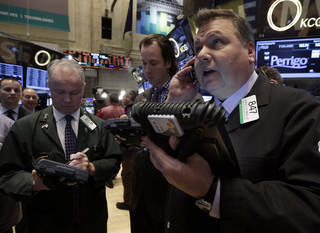 George Ettinger, right, works Monday with fellow traders on the floor of the New York Stock Exchange. AP photo Richard Drew -