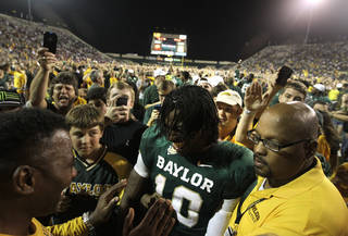 Baylor quarterback Robert Griffin III (10) is surrounded by fans that rushed the field and security as he is escorted off the field following their 45-38 win over Oklahoma in an NCAA college football game Saturday, Nov. 19, 2011, in Waco, Texas. (AP Photo/Tony Gutierrez) ORG XMIT: TXTG215