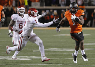 Joseph Randle (1) outruns Oklahoma's Tony Jefferson (1) during the Bedlam college football game between the Oklahoma State University Cowboys (OSU) and the University of Oklahoma Sooners (OU) at Boone Pickens Stadium in Stillwater, Okla., Saturday, Dec. 3, 2011. Photo by Chris Landsberger, The Oklahoman
