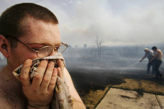 John Brewer holds a wet towel to his face after battling wild fires in his housing addition in Midwest City Thursday, April 9, 2009. Photo by Jim Beckel, The Oklahoman