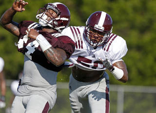 Mississippi State linebacker Benardrick McKinney (50) hits wide receiver Christian Holmes (44) during an NCAA college football practice in Starkville, Miss., Saturday, Aug. 10, 2013. High humidity mixed with high temperatures have marked most of the football training camps this summer. (AP Photo/Rogelio V. Solis) ORG XMIT: MSRS105
