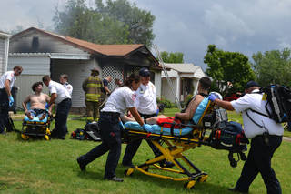 Paramedics attend to two men after a fire broke out Saturday in southwest Oklahoma City. Photo by Zeke Campfield, the Oklahoman