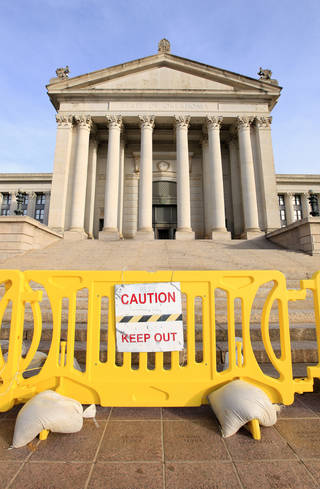 Barricades continue to block the south steps of the state Capitol. They were erected to protect the public from pieces of rock and mortar falling from the crumbling building. Photo by Paul B. Southerland, The Oklahoman PAUL B. SOUTHERLAND - PAUL B. SOUTHERLAND