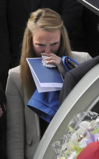 Sarah Harper, the girlfriend of Christopher Lane, looks into the funeral hearse at St. Therese's Church in Melbourne, Australia, Wednesday, Aug. 28, 2012. Lane died Aug. 16 in Duncan, Oklahoma, and police say three teenagers targeted him at random to break up the monotony of an Oklahoma summer. (AP Photo/AAP Image, Julian Smith)