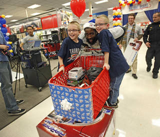 James Harden with the Oklahoma City Thunder shops with Jeremy Underhill, 7, left, and Jason Underhill, 7, during a shopping spree with the Sunbeam Family Services Grandparents Raising Grandkids program and the Thunder at a Target store in Oklahoma City, Thursday, December 16, 2010. Photo by Bryan Terry, The Oklahoman