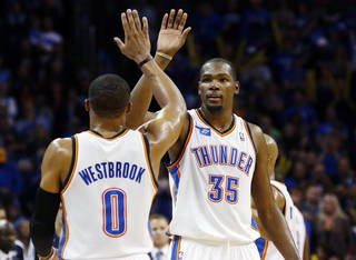 Oklahoma City Thunder forward Kevin Durant (35) high fives teammate Russell Westbrook in the fourth quarter of an NBA basketball game against the Phoenix Suns in Oklahoma City, Sunday, Nov. 3, 2013. Oklahoma City won 103-96. (AP Photo/Sue Ogrocki)