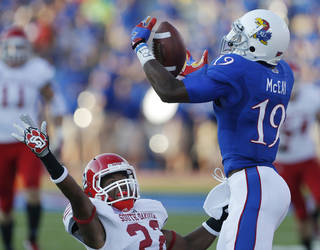 Kansas wide receiver Justin McCay (19) drops a pass while covered by South Dakota defensive back Jarrid Bryant (22) during the first half of an NCAA college football game in Lawrence, Kan., Saturday, Sept. 7, 2013. (AP Photo/Orlin Wagner)